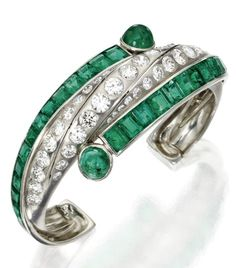 Art Moderne platinum, emerald and diamond cuff bracelet, circa 1930. The center band of bombé form set with round diamonds weighing approximately 6.25 carats, flanked by channel-set calibré-cut emeralds weighing approximately 12.50 carats, accented at the terminals by cabochon emeralds, internal circumference 6 inches.