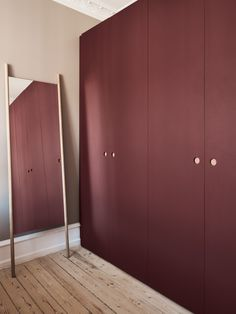 Reform's Basis wardrobe design in linoleum in color 'Burgundy' with natural oak handles and edges. It's an IKEA hack.