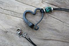 Each heart is made by hand in a coal forge, shaped on the anvil, brushed, and finished with wax to prevent rusting and add shine.....a one of a kind piece of Art. Horse shoe nail heart hung from an 18 inch cotton cord with an African turquoise accent bead. Fastens with an antiqued silver plated lobster clasp.
