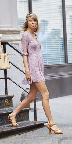 Leaving her New York City apartment in a pink lace dress, jeweled headband, and nude heels.   - ELLE.com