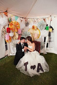 DIY Photobooth in the corner of a tent reception - lots of fun! Check out those huge pinwheels!