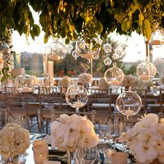 Garden-Inspired Reception Space. White Lilac Inc. filled the open-air reception space with low arrangements of white orchids and hydrangeas. Above, greenery and vines wrap around hanging glass candles. Paired with mirrored tables, the space is filled with a romantic glow (with a little help from the California sunset).