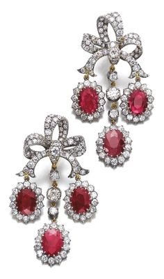 A pair of antique ruby and diamond earrings, late 19th century composite. Of girandole design, each bow surmount set with circular-cut diamonds, supporting oval rubies framed within similarly cut diamonds, post and hinged back fittings. #antique #earrings