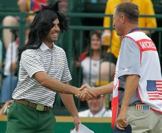 International team player Charl Schwartzel, left, of South Africa, wears a wig onto the first tee as he greets caddie Jim Mackay, Thursday. (Jay LaPrete/AP)