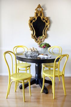 Chic dining room with gold rococo mirror, glossy black pedestal table and canary yellow Thonet Bentwood Chairs. Painted Kitchen Tables, Painted Chairs, Painted Furniture, Cane Furniture, Furniture Showroom, Furniture Design, Bentwood Chairs, Wicker Chairs, Wooden Chairs
