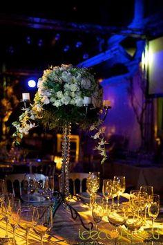 Hermoso centro de mesa alto en herreria de cristal, hehco con rosas, orquídeas y follaje. Ideal para una boda elegante.