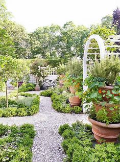 Lush, organic garden with winding gravel paths and an ivy-covered archway. #potagergarden