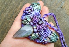 A beautiful necklace sculpted from durable clay, made with love by me. She has a lilac purple labradorite and a dark purple amethyst facet. Adorned with Swarovski crystals and strung on a braided macrame cord with amethyst beads.   Amethyst: ~Dreams ~Meditation ~Protection ~Overindulgence ~Connection to Divine  Labradorite: ~Mysticism  ~Psychic abilities  ~Stone of shamans, witches, seers ~Bridge between air & earth, grounding in psychic impressions ~Helps see what was previously in the…