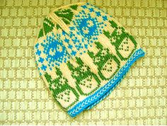 A Norwegian-style hat with colorwork featuring Totoros, soot sprites, and acorns from My Neighbor Totoro.
