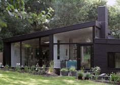 Architects Takero Shimazaki and Charlie Luxton renovated a 1960s house outside London to create a modern home that features black-painted brickwork, large windows and a new angular roof