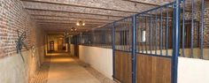 Brick stable barn with blue finish to steel stalls; good use of spot lighting