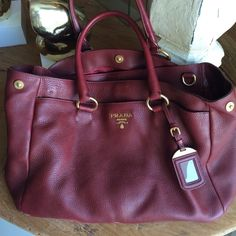 Prada handbag in Crimson with gold detail Timeless Prada handbag in vampy Crimson color with gold detail. Would say this is a medium sized purse with 4 compartments. Comes with a strap to wear long. It has some wear at the bottom (so I will be willing to negotiate the price ). Prada Bags Hobos