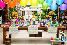mesa de doces inspirada no tema arco-íris para aniversário infantil 5 anos com doces temáticos.