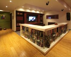 Basement storage idea. Wow. Love the books around this wall! Could either be a bar or put a sectional on the other side.