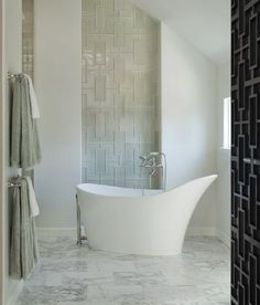 love how the wall tiles mirror the fretwork on the wood door. Love the V and A tub!