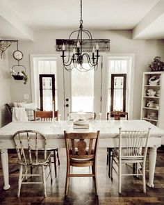 A gorgeous rustic inspired farmhouse kitchen with a vintage feel. Love the mixed matched dining chairs and that hanging grocery scale clock by Farmhouse Style Kitchen, Modern Farmhouse Kitchens, Rustic Farmhouse, Farmhouse Ideas, Rustic Kitchen, Kitchen Dining, Kitchen Cabinets, Dining Room Design, Dining Room Table