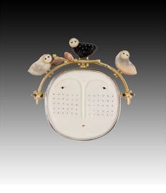 "Pin/Pendant | Carolyn Morris Bach.  ""Face with owls"" 18K, 22k, Sterling, Bone, Fossilized Ivory, Ebony"