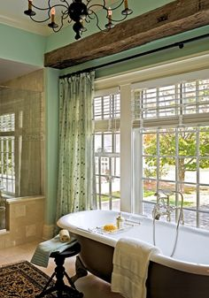 Exposed beam above a classic claw foot tub and a wall of windows to illuminate the vast bath