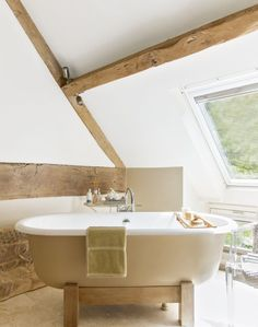 Hotel-inspired Bathroom with Roll-top Bath and Exposed Beams