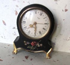 This is an antique German Made, Musical, wind up alarm clock with a black wooden case and a painted floral design.