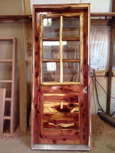 Rustic custom Red Aromatic Cedar exterior door with family brand. Log frame in window.