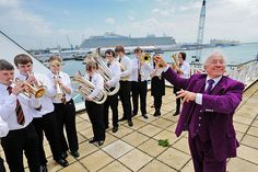 Simon Callow pictured as he is conducting the Southampton University Brass band. with the Royal Princess cruise ship docked in the background Royal Princess Cruise Ship, Princess Cruises, Simon Callow, Brass Band, Southampton, Actors, University, Pictures, Image