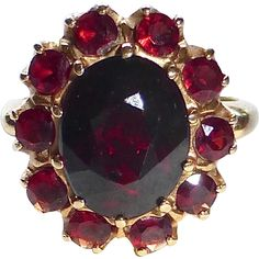 A lovely Victorian Revival ring beautifully made in 14k yellow gold and set with eleven natural garnets. The cluster has a large faceted oval garnet