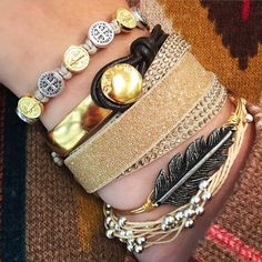 """Audrey's @ South Hills Village on Instagram: """"#SuperStackSunday Our """"Social Media Sarah"""" is glittering in gold with her beautiful stack of gold and beige bracelets. Products featured(top to bottom): My Saint My Hero- Benedictine Blessing Tan/Mixed Medals Uno de 50- Cowboy Swarovski- Slake Duo in Gold Luca and Danni- Lucky Feather Pura Vida - Platinum in Cream So stop into Audrey's at South Hills Village and pick up your favorite gold nugget today !!"""""""