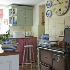 Small kitchen with neutral splashback tiles, pale green cabinetry, grey range cooker and red gingham soft furnishings