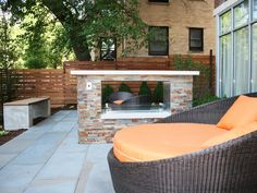 A contemporary see-through fireplace makes a strong centerpiece in this small outdoor patio, which also features round wicker lounge chairs with orange cushions.