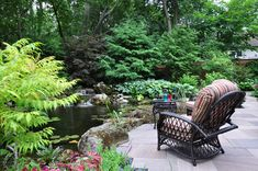 A stone patio runs along the back of the house and overlooks the pond.