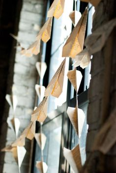 "paper airplane garland from old book pages--I see this as book paper airplanes hung from fishing line strung across the display case with a sign that says ""Let your imagination soar with a good book"""
