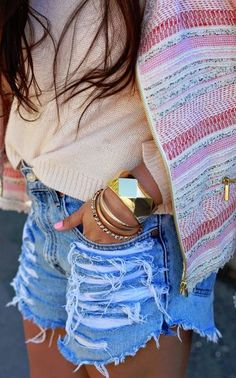 Really like the ripped jean shorts with the clean jewelry and sweater.