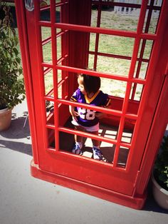 A young Viking's fan in the red phone booth at Training Camp | #VikingsInUK
