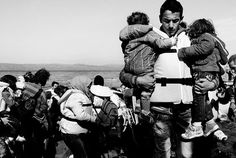 A Syrian man carries his two children from the boat after landing.