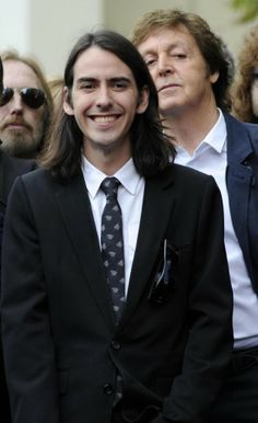 Dhani smiling at the Hollywood Walk Of Fame ceremony for his dad's star. Paul McCartney & Tom Petty are directly behind him.