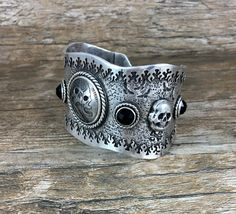Dead Men Tell No Tales.....What a wonderful piece of pure badassery!  This sterling silver textured cuff showcases a 1938 buffalo nickel, masterfully carved into a work of art. Notice the 2 pirate faces!  Rose cut onyx and hand forged skulls flank the sides of the coin. The skull and bezel settings are made of fine silver.  The hand stamped birds, cross bones and border really add to the feel of boating with pirates. The fire bezel border finishes this cuff beautifully. The only thing…