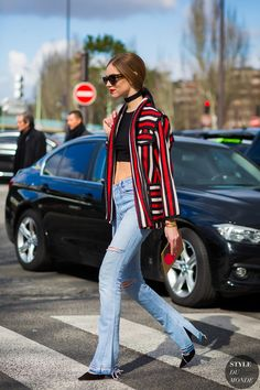 Vertical bold stripes paired over a black crop top with ripped flare jeans and a black choker makes for statement street style.