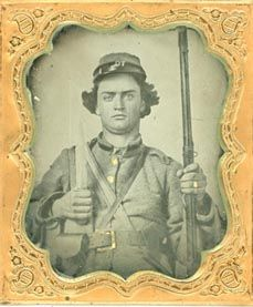 """1ST GEORGIA, TAHNALL GUARDS, PVT. JAMES JEFFERSON SMITH, 1/6th plate tintype in a thermo plastic case. Jefferson was from N. Augusta, GA. Olmsteads 1st Georgia, Tahanall Guards. Smith poses holding upright a bowie knife as well as his musket. On his belt is a large Georgia frame buckle and his cap box. Published in """"Still in More Confederate faces"""", excellent detail and contrast."""