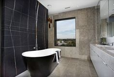 Wooden vanity walls, stone washbasin and a warm stone bathtub, with properly placed light scones are some of the stone bathroom design ideas. Modern Bathtub, Modern Bathroom Design, Black Bathtub, Freestanding Bathtub, Classic Bathroom, Bathroom Designs, Bathroom Trends, Bathroom Interior, Bathroom Ideas