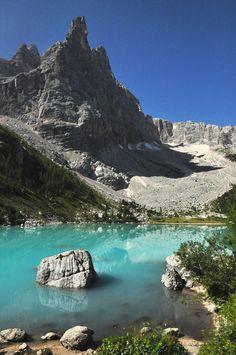 """Il lago del Sorapiss sulle Dolomiti, è adagiato in uno dei più spettacolari anfiteatri di queste fantastiche montagne. Poco sotto i 2000 metri, è caratterizzato da un particolare colore celeste pastello dato dal limo glaciale perfettamente bianco del suo fondale.  Lo sovrasta una straordinaria guglia denominata """"Dito di Dio"""", alta 2603 metri."""