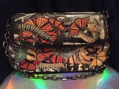 Covered with monarch butterflies and caterpillars (yes some sneaky Viceroys too) all forms of their magical transformation super colorful with a barely peeking through black and white background. Medium-smallish bag with 3 inner pocket compartments one that zips. Bag has a zipper closure plus a flap with magnetic snap. Strap is gunmetal chain but I can substitute for a different one if you desire. I can make just about any themed bag any size to order for you. Special order requests are…