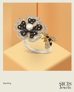 The beauty of the botanical world takes shape as a vibrant cocktail ring, with delicate micromosaic petals surrounding a heart of pearl, set off by a breezy bee. Bee Ring, Pearl Set, Cocktail Rings, Creative Design, Bag Accessories, Delicate, White Gold, Vibrant, Shapes