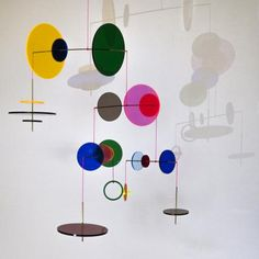 LMC is an exploration on Light, Movement, and Color in the form of a mobile. Discs of acrylic glass in different colors and sizes are mounted on brass tubes hanging from pink or yellow thread. Those discs are arranged randomly, so it is the balance itself that defines the harmony of the piece. When exposed to direct light, each disc colors its shadow while reflecting that light across the room, perfect to celebrate that time of the day when the sun shines through your window. Although they…
