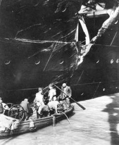 Workers inspect the damage to RMS Olympic caused by her collision with HMS Hawke