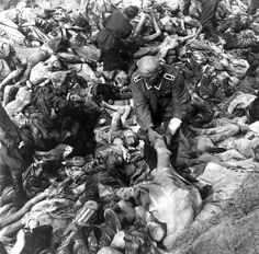 A German SS guard, standing amid hundreds of corpses, hauls another body of a concentration camp victim into a mass grave in Belsen, Germany in April of 1945.