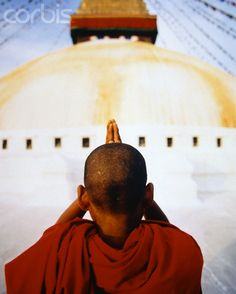 Young Buddhist Monk Praying in Front of Stupa
