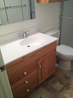 Bathroom Remodel: standard sink; white countertop; tan wooden cabinets