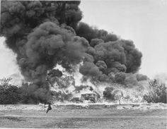 A demonstration of 'Fougasse', somewhere in Britain. A car is surrounded in flames and a huge cloud of smoke. In the foreground, a soldier can be seen running from left to right.