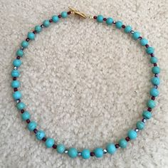 Turquoise and Gold Necklace This is a chalk turquoise bead, about 8 mm, interspersed with iridescent red Czech glass spacers. Hammered gold tone toggle clasp. Simple. Beautiful. Price is firm. JJJewels Jewelry Necklaces